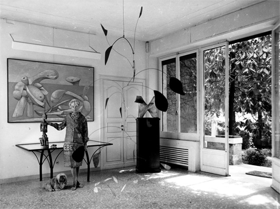 28th December 1961: American art collector and millionairess Peggy Guggenheim (1898 - 1979) in the entrance hall of her eighteenth century Venetian palace, the 'Palazzo Venier dei Leoni'. Hanging from the ceiling is a 1941 Alexander Calder mobile and behind her is a 1937 painting by Picasso 'On The Beach'. (Photo by Keystone Features/Getty Images)